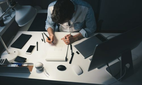 Designer at work in office. Man drawing in note pad
